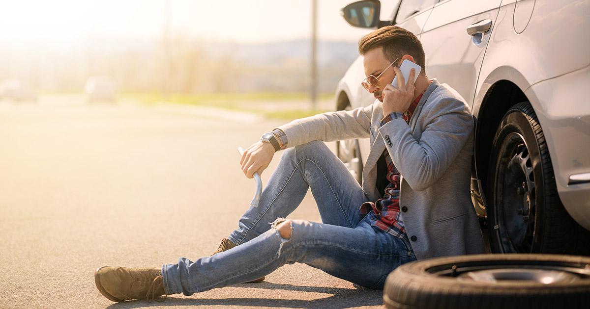 muškarac telefonom traži pomoć na putu