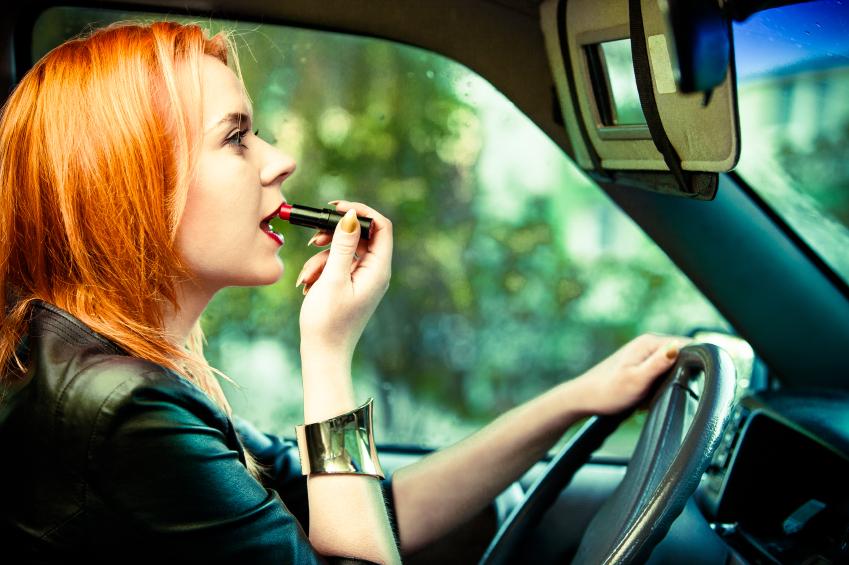 Devojka koja se šminka dok vozi auto